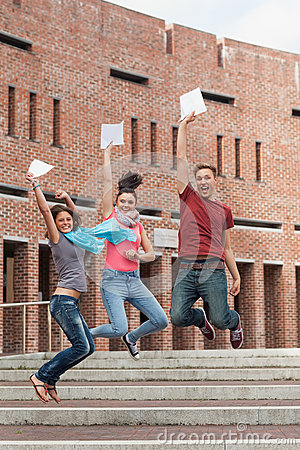 Happy students jumping in the air holding exam