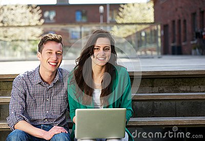 Happy students sitting outdoors with laptop