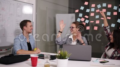 Happy successful young people business team giving a high fives gesture as they laugh and cheer their success at project. Front view stock footage