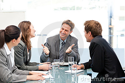 Happy team laughing together at a meeting