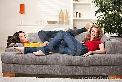 Happy teen girls smiling on sofa
