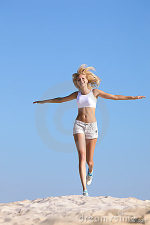 Happy teen running on beach