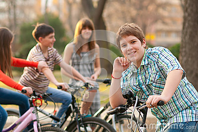 Happy teenage boy on bicycle with friends