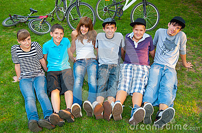 Happy teenage boys and girls resting in the grass
