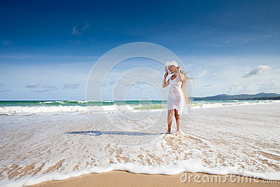 Happy teenage child in white dress on beach