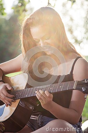 Free Happy Teenage Girl Playing A Guitar Royalty Free Stock Image - 123746756