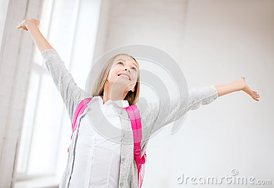 Happy teenage girl with raised hands