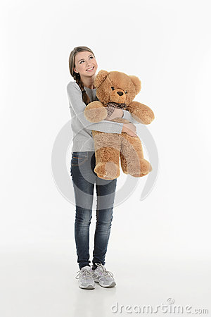 Happy teenage girl with teddy bear. Full length of cheerful teen