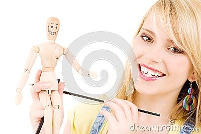 Happy teenage girl with wooden model dummy
