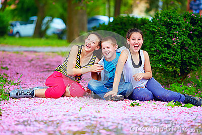 Happy teenage kids having fun in blooming park