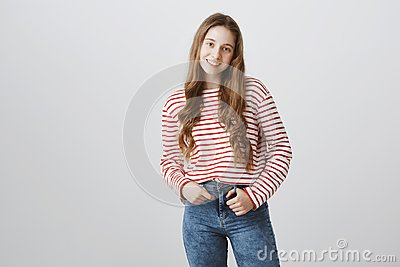 Happy teenage years. Portrait of young pretty blonde girl in trendy striped sweater holding hand in pocket and smiling Stock Photo