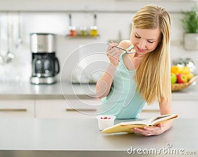 Happy teenager girl reading book and eating yogurt