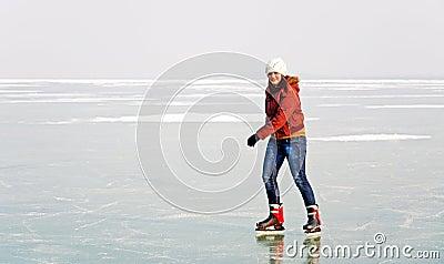Happy teenager girl is skating on frozen Lake Bala