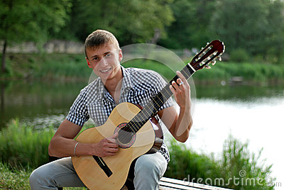 Happy teenager with a guitar by the river