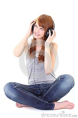 Happy teenager with headphones sitting