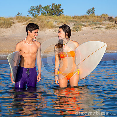 Happy teenager surfer couple on the beach shore