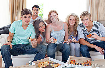 Happy teenagers eating pizza in the living-room