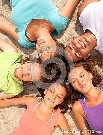 Happy teenagers lying on a sandy beach