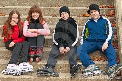 Happy teenagers in roller skates sitting outdoor