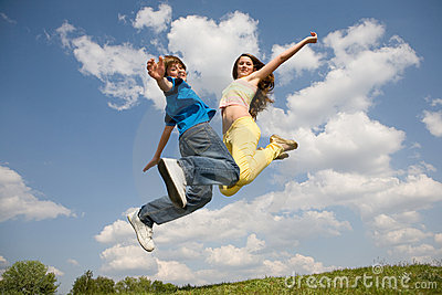 Happy teens - jumping under blue sky. Soft focus.