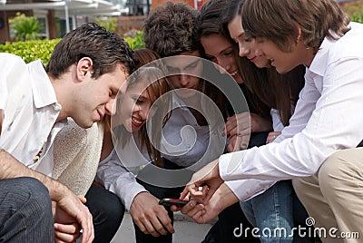Happy teens sitting on street