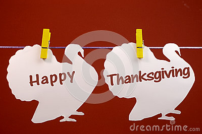 Happy Thanksgiving message greeting written across white turkeys hanging from pegs on a line