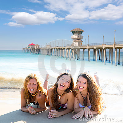 Happy three friends girls lying on beach sand smil