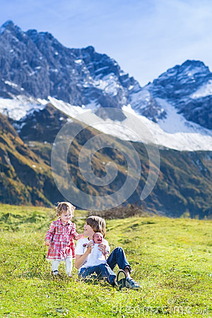 Happy three kids in field between snow mountains