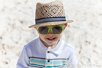 Happy toddler boy on white sand beach