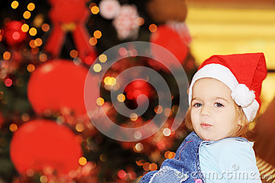 Happy toddler girl in front of xmas tree