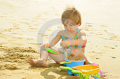 Happy toddler girl playing with her toys at beach