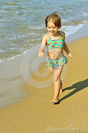 Happy toddler girl running on beach