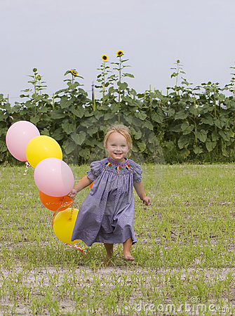 Happy toddler running with balloons in field