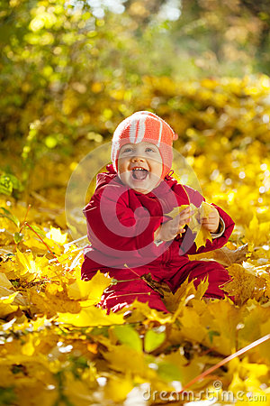 Happy toddler sitting on maple leaves Stock Photo