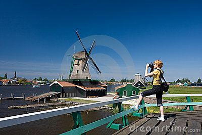 Happy tourist with photo camera and Dutch mill on