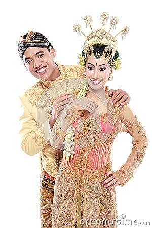 Happy traditional java wedding couple husband and wife embrace e