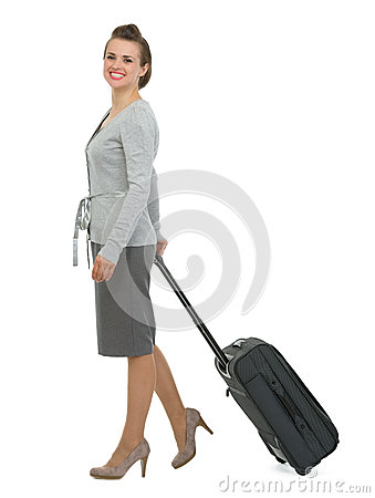 Happy traveling woman with suitcase walking sidewa