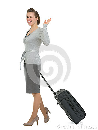 Happy traveling woman with suitcase waving hand