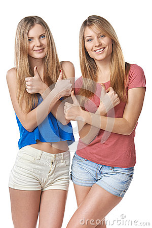 Happy two girl friends gesturing thumbs up