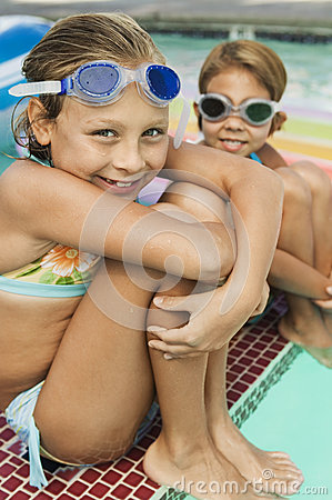Happy Two Girls Wearing Swim Goggles By Pool