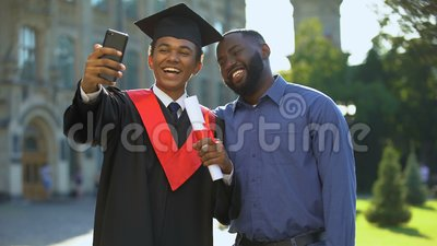 Happy university student graduation mantle and father taking selfie smartphone. Stock footage stock video