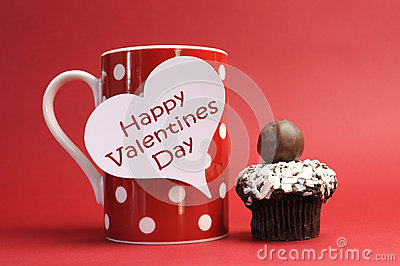 Happy Valentines Day message on red polka dot mug with chocolate cupcake