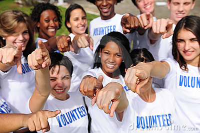 Happy volunteer group pointing towards camera