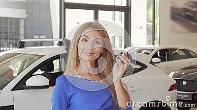 Happy weiblicher Fahrer zeigt Autoschlüssel an der Kamera nach dem Kauf eines neuen Autos stock video