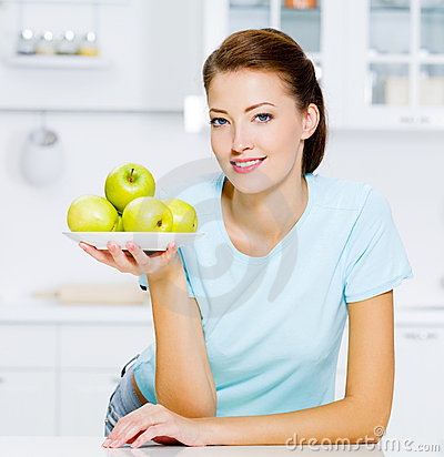 Happy woman with apples on a plate