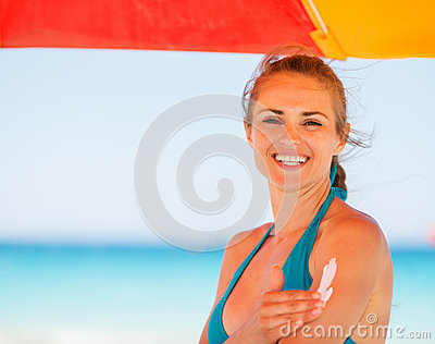 Happy woman applying sun block creme on arm
