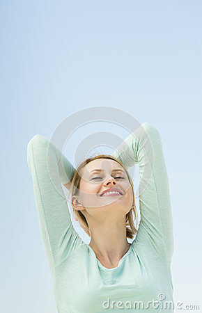 Happy Woman With Arms Raised Against Clear Sky