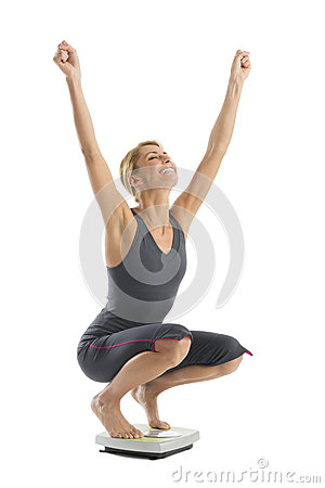 Happy Woman With Arms Raised Crouching On Weight Scale