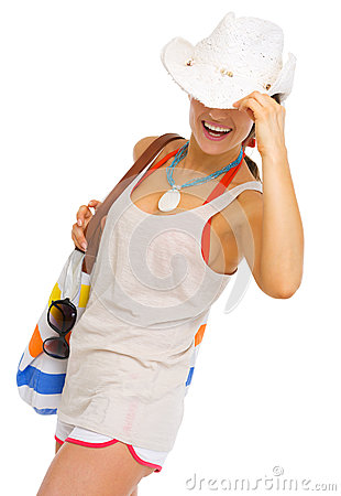 Happy woman with bag hiding behind hat