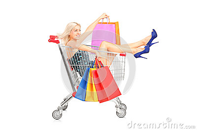 Happy woman with bags sitting in a shopping cart